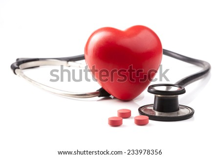 Red heart with stethoscope and red pills isolated on white background - stock photo