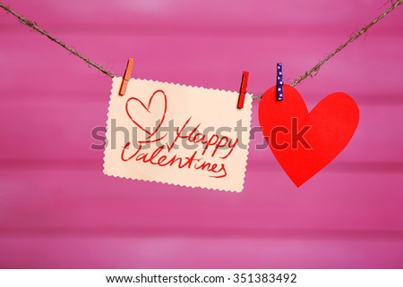 Red hearts and blank note, on wooden background - stock photo