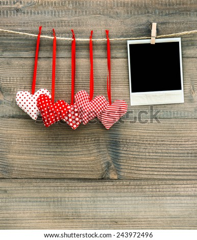 Red hearts and vintage polaroid photo frame. Handmade Valentines Day decoration - stock photo
