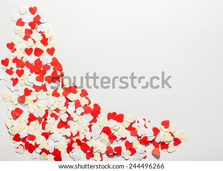 Red hearts confetti on white background.hearts in the corner