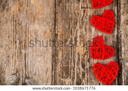 Red hearts on an old wooden background. Border.Greeting card for Valentine's Day, Wedding or Birthday