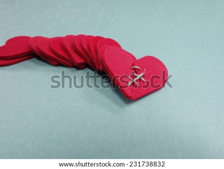 Red hearts with one stiched, on blue                                - stock photo