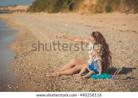 Red heir young mother with small daughter sitting on a sandy beach enjoying good sunny day. Mother is showing by her hand in forward. - stock photo