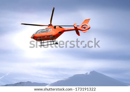 Red helicopter flies over snow capped mountain summits - stock photo