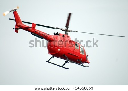 red helicopter is airborne - stock photo