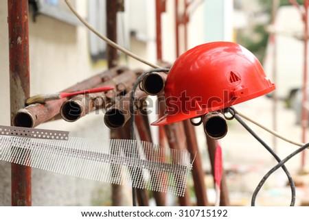 red helmet on tubular scaffolding, shallow DOF - stock photo