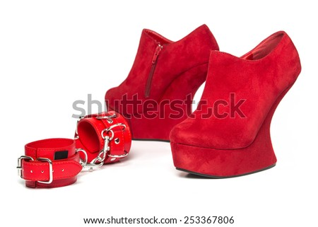 Red high heels shoes with platform in wedges style and red hand cuffs and a leather whip for sexual roleplaying,   - stock photo