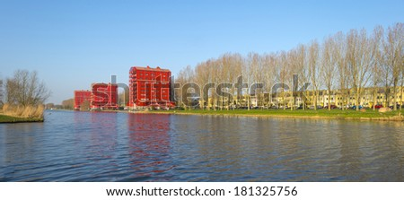Red highrise along a canal in summer - stock photo