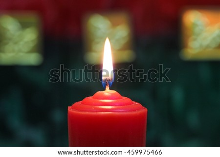 Red  holiday candles with red, gold and green texture background; Christmas and spiritual concept - stock photo