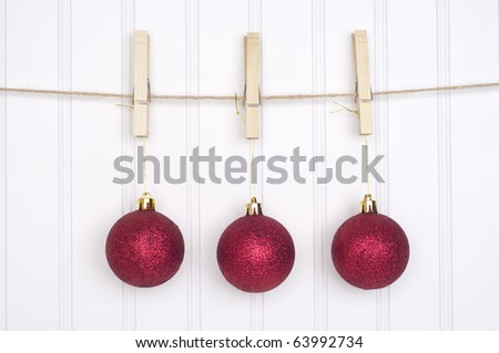 Red Holiday Ornaments Hanging on a Clothesline on a White Background. - stock photo