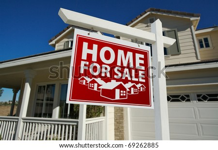Red Home For Sale Real Estate Sign and House Against a Blue Sky. - stock photo