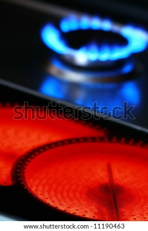 Red hot ceramic stove electric cooker and blue flames of gas stove - stock photo