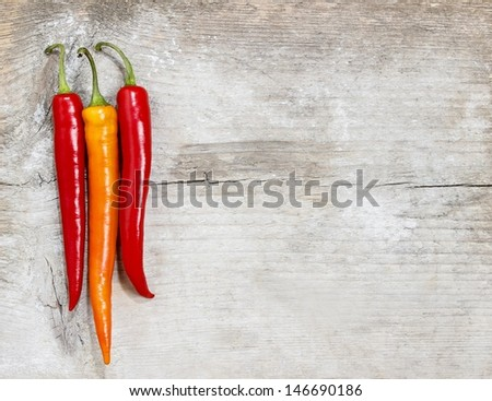 Red hot chili peppers on old wooden table - stock photo