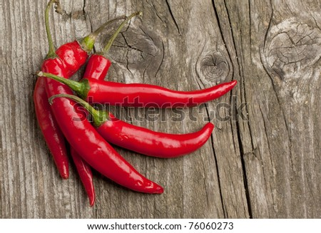 Red hot chili peppers on old wooden table