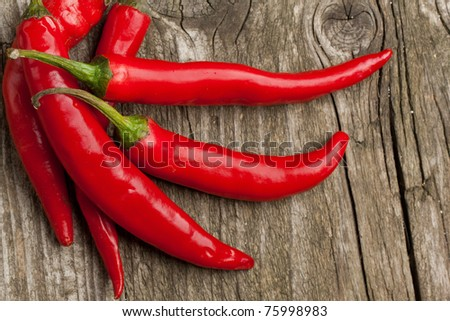 Red hot chili peppers on the wooden desk - stock photo