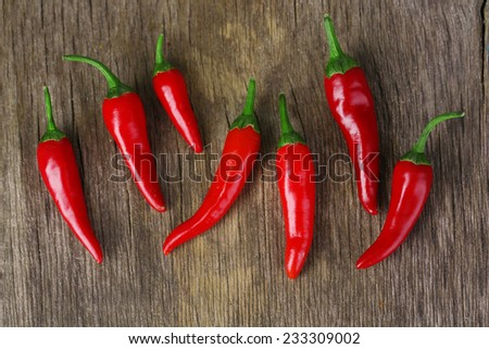 Red hot chili peppers on wooden background - stock photo