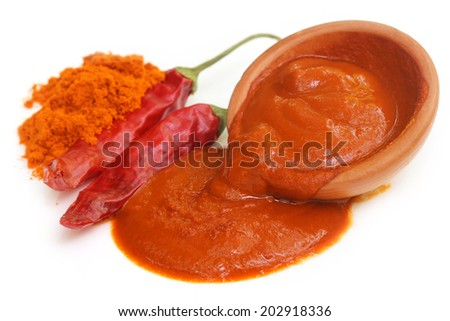 Red hot chilies with paste over white background - stock photo