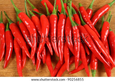 Red hot chilli peppers on the chopping board . - stock photo