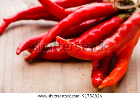 Red hot chilli peppers on wooden table - stock photo