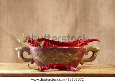red hot chillies pepper in old wooden bowl, shallow dof