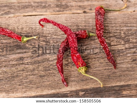 Red hot dry chili peppers on old wooden table