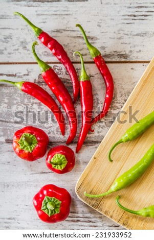 Red hot peppers and green peppers over white wooden background - stock photo