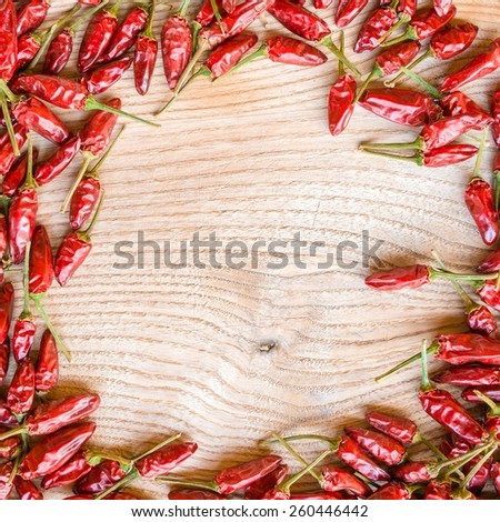 Red hot spicy chillies on wooden background with shadow contrast - stock photo