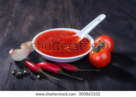 red hot sweet chilli sauce over old wooden background - stock photo