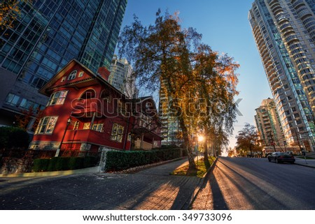 Red house in the midst of tall, glass buildings and sun peeking through the tree - stock photo