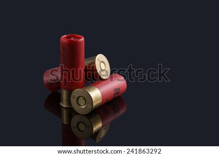Red hunting cartridges for shotgun on a black background - stock photo