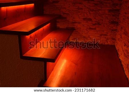 Red illuminated wooden stairs - stock photo