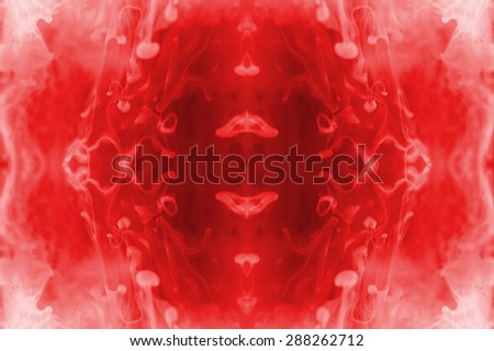 Red ink forming patterns resembling Rorschach Test ink blots. - stock photo