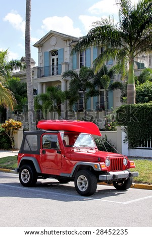 Red Jeep with kayak parking in front the house - stock photo