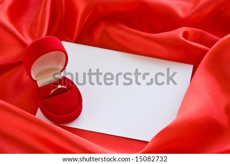 Red jewerly  box with ring and empty card on red satin - stock photo