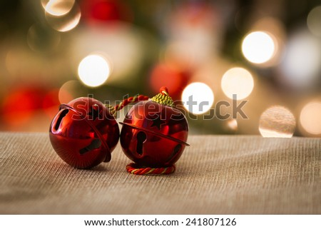 Red Jingle Bell against Christmas tree - stock photo