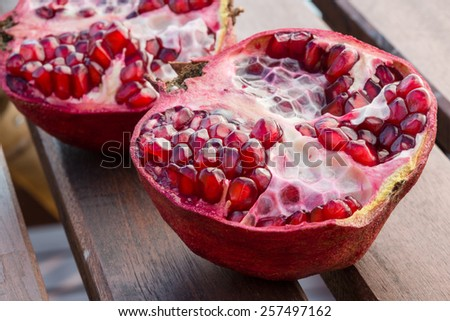 Red juicy pomegranate  fruit on wooden table - stock photo