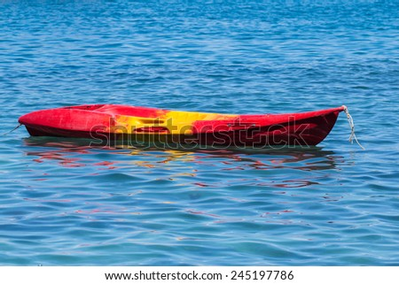 Red kayak floating over blue sea - stock photo