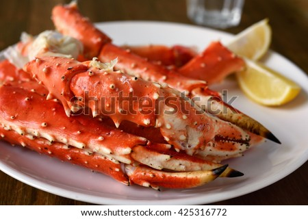 Red king crab legs with lemon on a plate