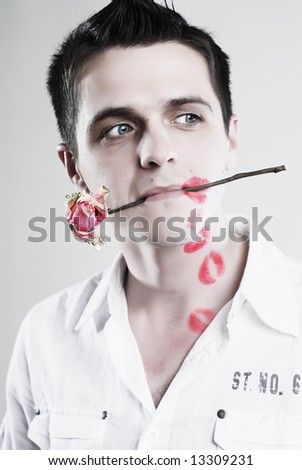 Red kisses on face of young man with rose at white background - stock photo