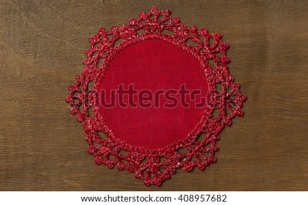 Red knitted flax table napkin handmade on wood background - stock photo