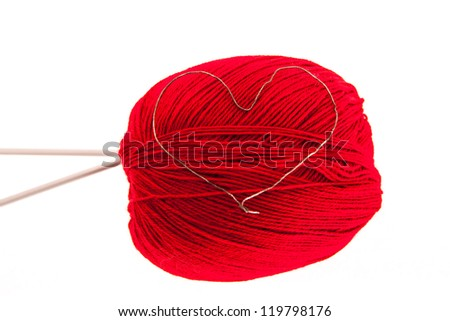Red knitting yarn with needles and a heart isolated on white