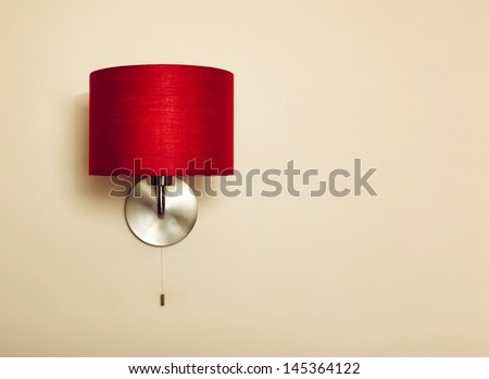 Red lamp on beige wall background - stock photo