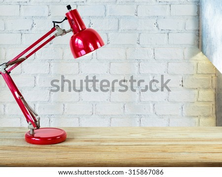 Red lamp on wooden table top over brick wall background/ Interior decoration concept - stock photo