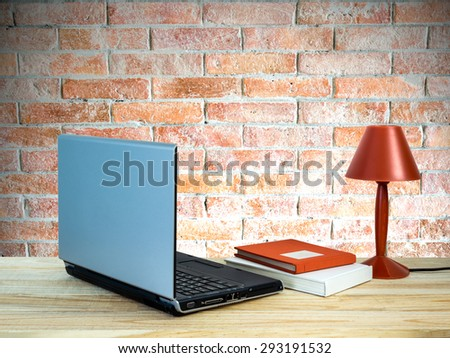 Red lamp with laptop computer, books on wooden table top over brick wall background/ interior still life - stock photo
