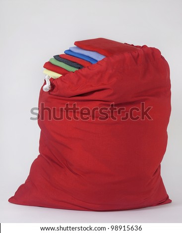 Red Laundry Bag with Brightly Folded Shirts Piled on Top of Each Other