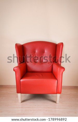 Red leather armchair against the wall on wooden floor - stock photo