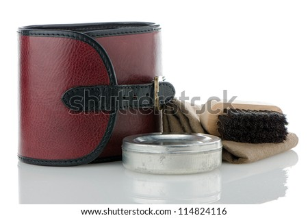 Red leather bad and container of shoe polish and brush on white background. - stock photo