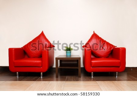 Red leather chairs with pillow, a plant in a pot on a table - stock photo