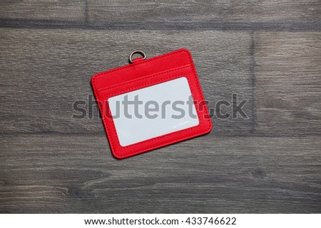 Red Leather Name Tag on wooden table. Top view. - stock photo