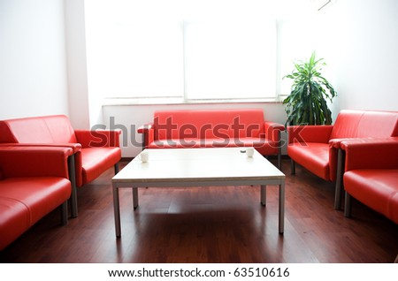 Red leather sofa and white table at waiting room. - stock photo